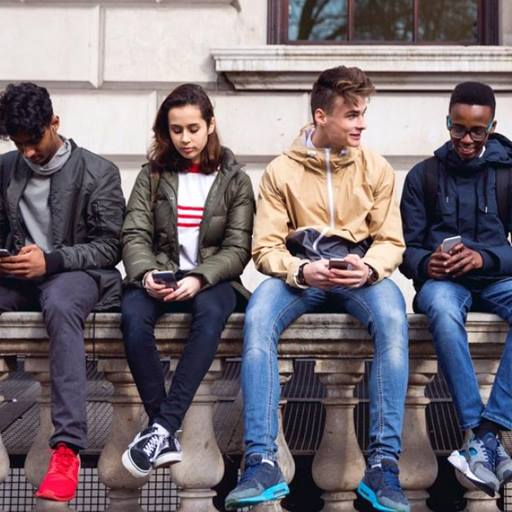 Picture of four young people sitting on a  wall, chatting and checking their phones