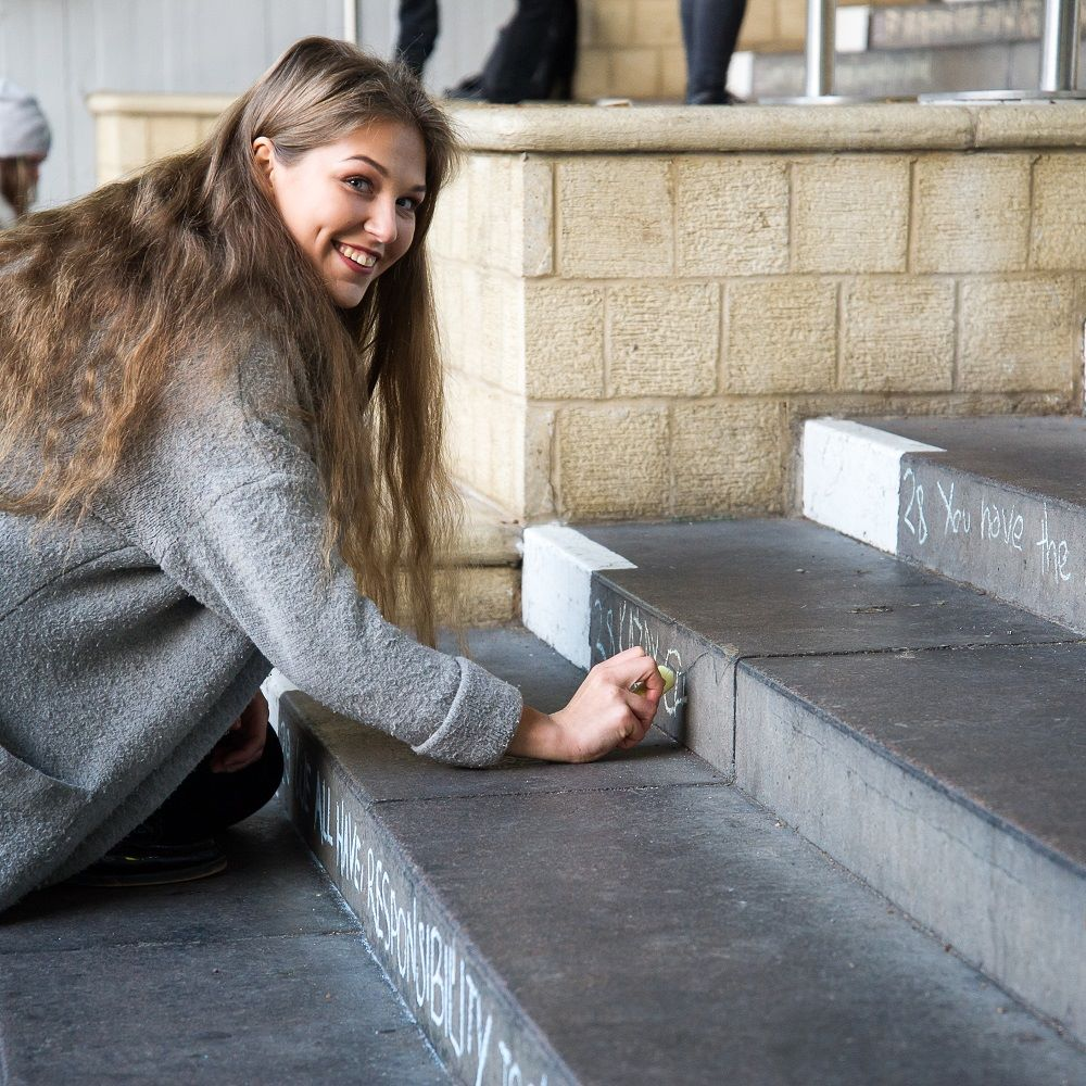 Student chalking the steps during Human Rights week
