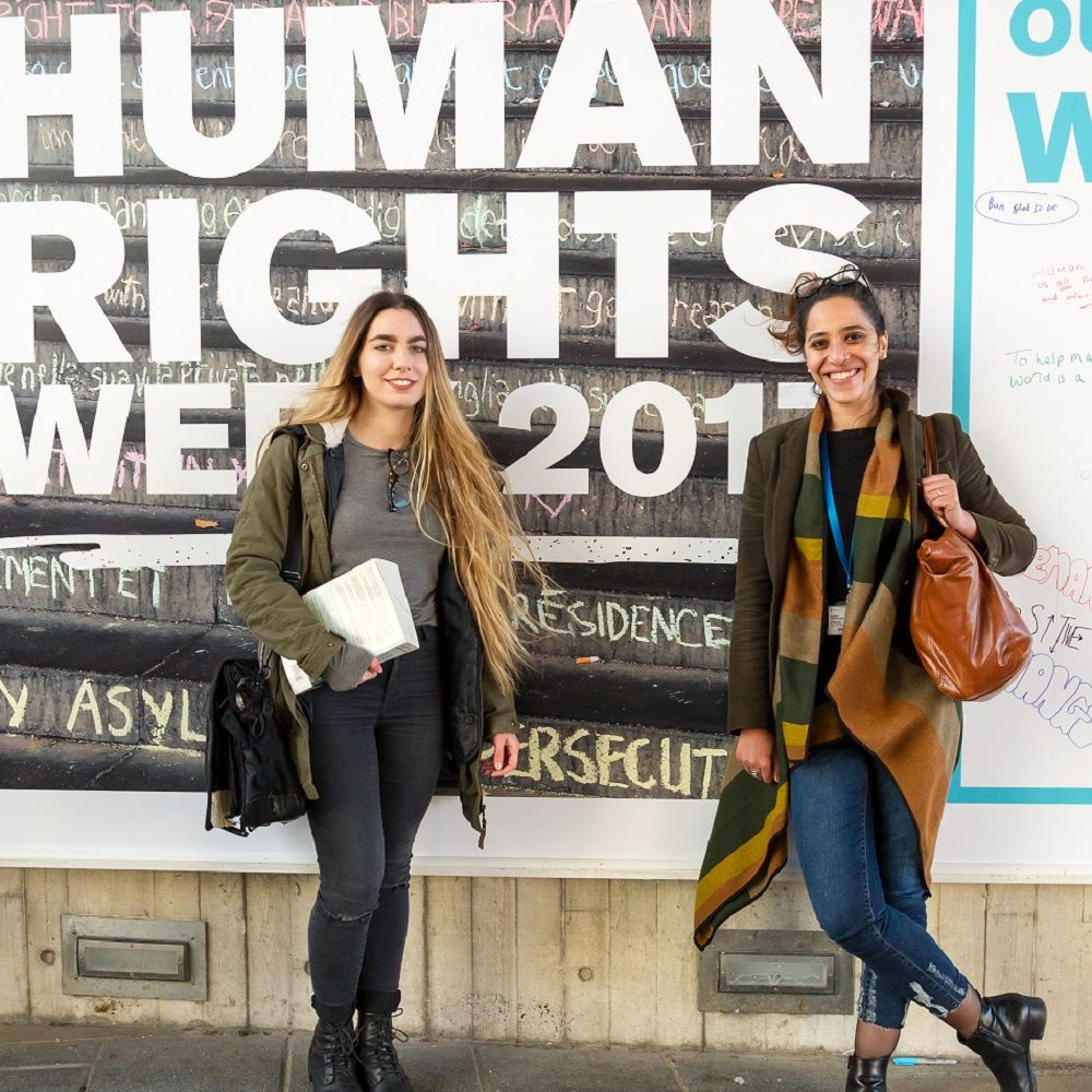 Two students standing against Human Rights week poster