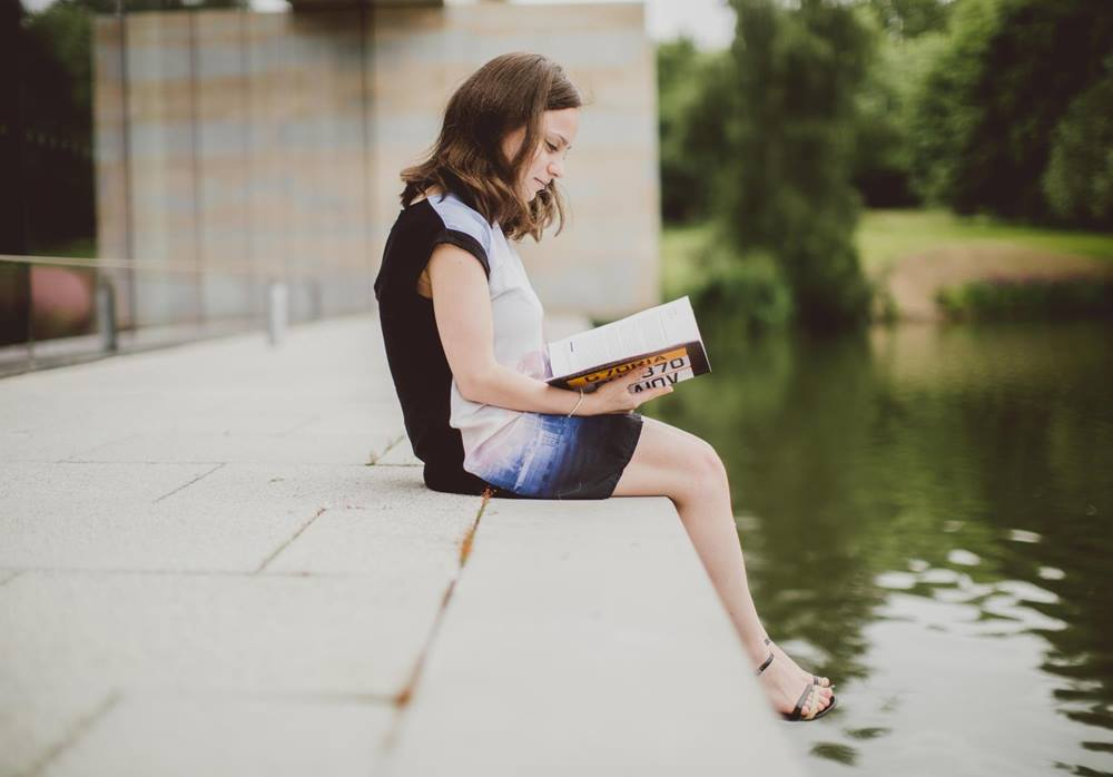 Student reading by the lake