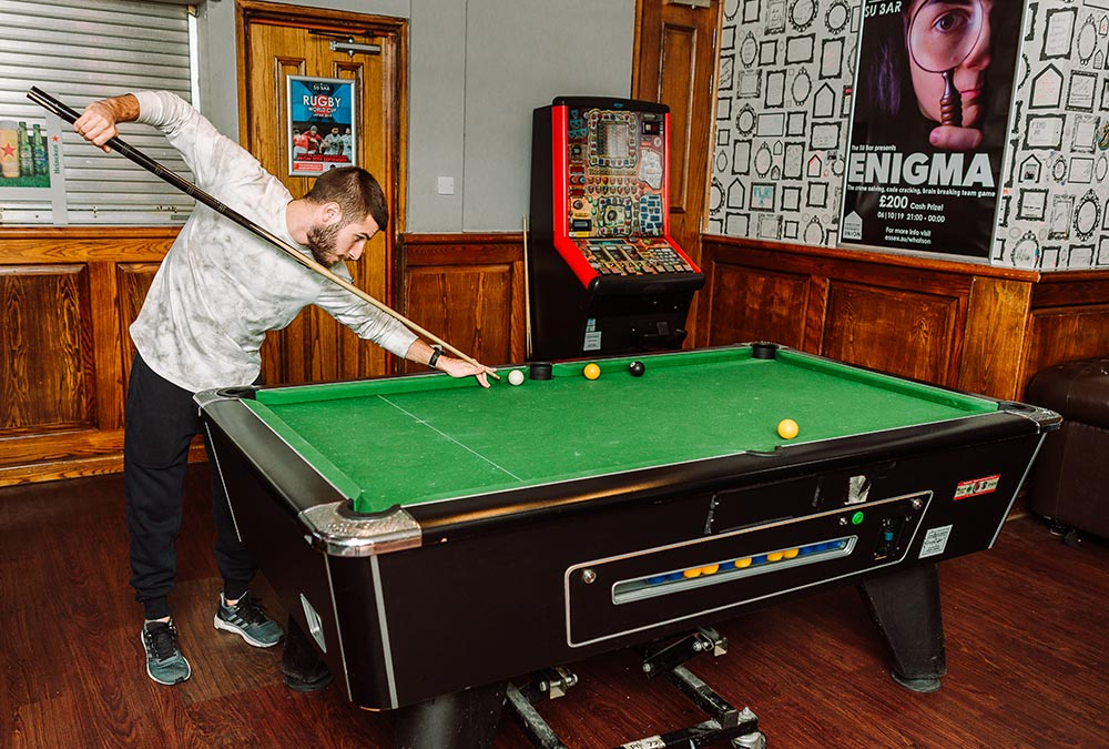 Student playing pool in the SU Bar)