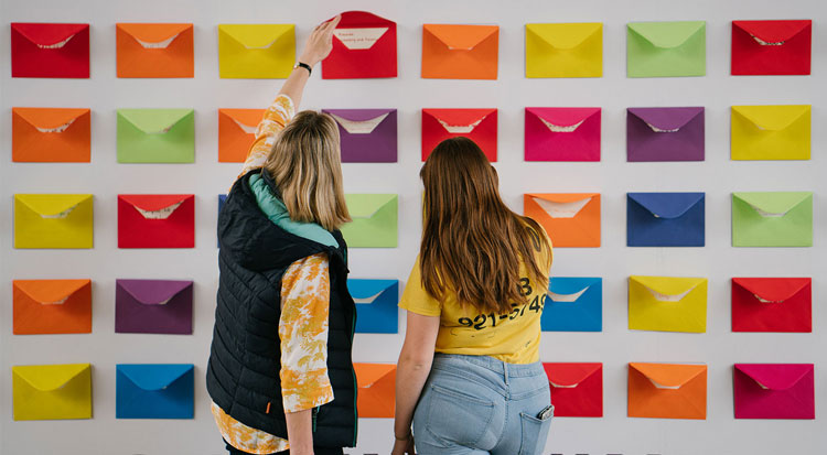A student and parent/guardian opening envelopes on wall which contain messages from our current students