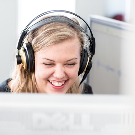 Student wearing headphones smiling at a screen